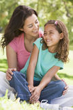 Woman and young girl sitting outdoors smiling Stock Images