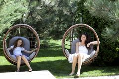 Woman and young girl sitting on patio Stock Photo