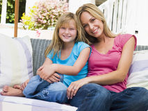Woman and young girl sitting on patio smiling royalty free stock images
