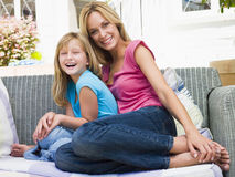 Woman and young girl sitting on patio smiling Stock Photos