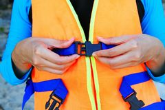 Woman or young girl wearing orange life vest or life jacket. Before going to swimming or scuba diving in the sea- Close up and focusedhands. Safety life and royalty free stock photo