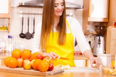 Woman housewife in kitchen cutting apple fruits Stock Photography