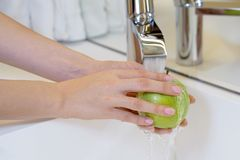 A girl washes an apple under the tap royalty free stock image