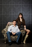 Woman and young man sitting in ancient armchair Royalty Free Stock Image