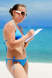Young woman with notebook on a beach Stock Image
