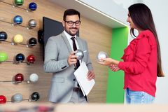 Woman and salesman looking at a color palette in a car dealership. Woman and young salesman looking at a color palette in a car dealership royalty free stock photo