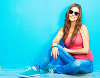 Woman in youth style sitting on a floor Stock Photography