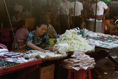 Woman at Zegyo Market arraging her goods. ZEGYO MARKET/MANDALAY, MYANMAR JAN 22, 2016: A Women selling some sort of tailor`s chalk is gently arranging her goods Stock Image