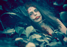 Woman zombie portrait. Outdoors. Dark lighting. Color was changed to emphasize the atmosphere of horror Stock Photo