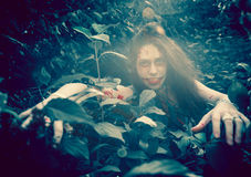 Woman zombie portrait. Outdoors. Dark lighting. Color was changed to emphasize the atmosphere of horror Royalty Free Stock Images
