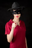 Woman with zorro mask pointing you. Young woman with zorro mask wearing red dress pointing you Royalty Free Stock Image