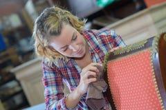 Womanan que trabaja en taller de la tapicería foto de archivo