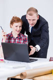 Womanand man sitting close to the drafting board in front of the laptop Stock Image