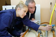 Womanas apprentice beeing tested by craftsman. Man stock images