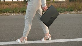 Womanbusinessman carries in his hand black briefcase, woman in trousers and a jacket walks along asphalt, side view. Womanbusinessman carries in his hand black royalty free stock photography