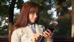 Womanbusinessman verifica o email na tabuleta no parque do verão em um banco video estoque