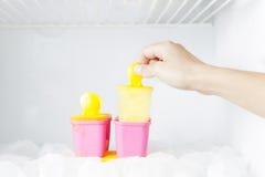 Womand-Hand, die eine Eiscreme von frigde hält Lizenzfreies Stockfoto