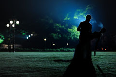 Womand and man silhouettes in the evening park Stock Photography