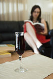 Womang relaxing. Glass of red wine and woman reading a book on the background. Glass in focus, woman out of focus royalty free stock image