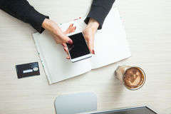 Womanhand держа smartphone и используя пластичную кредитную карточку Стоковые Фото