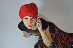 Beautiful Gypsy - Eastern woman in red turban, gir. The woman - girl talking on the phone Royalty Free Stock Images