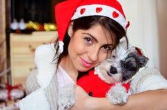 Womanhugging jej pies ubierał z czerwonymi boże narodzenie kapeluszami Zdjęcie Stock