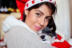 Womanhugging jej pies ubierał z czerwonymi boże narodzenie kapeluszami Fotografia Stock