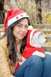 Womanhugging jej pies ubierał z czerwonymi boże narodzenie kapeluszami Obraz Royalty Free