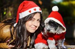 Womanhugging jej pies ubierał z czerwonymi boże narodzenie kapeluszami Fotografia Royalty Free