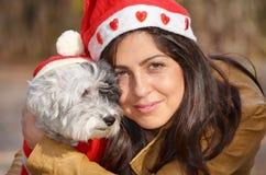 Womanhugging jej pies ubierał z czerwonymi boże narodzenie kapeluszami Obrazy Royalty Free