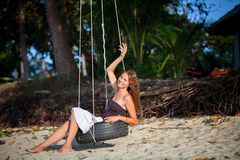 Womani sitting on the swing on paradise beach Stock Images