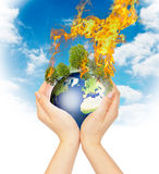 Womanish hands holding burning Earth. Stock Photography