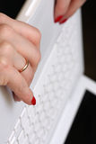 Womanish hands on a white laptop. Wedding ring clo Stock Photo