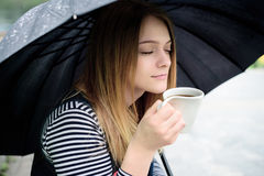 Womanl喝芬芳咖啡高兴地在伞下 免版税库存照片