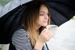 Womanl beve il caffè fragrante con piacere sotto l'ombrello Fotografie Stock Libere da Diritti