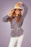Womanl bonito joven con el atuendo retro que toca su sombrero Foto de archivo libre de regalías