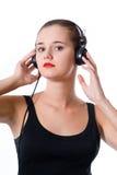 Womanl de brune avec des écouteurs sur le fond blanc images libres de droits