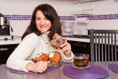 Womanl eating a bun Stock Photos