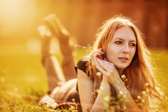 Womanl in a grass with flowers Stock Photo