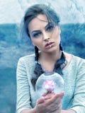 Womanl guarda uma garrafa de vidro na geada com uma rosa para dentro Fotografia de Stock Royalty Free