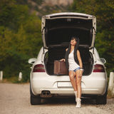 Womanl med resväskan nära bilen Fotografering för Bildbyråer