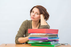 Womanl office staff thoughtfully leaning on a stack of folders Stock Images