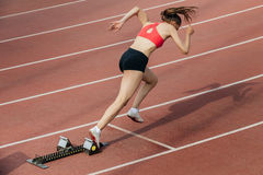 Womanl sprinter start at 400 meters. Woman sprinter at start of 400 metres at stadium Royalty Free Stock Image