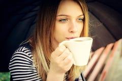 Womanl trinkt wohlriechenden Kaffee mit Vergnügen unter Regenschirm Lizenzfreie Stockfotos