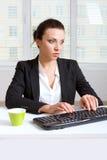 Womanl in vestiti convenzionali che scrivono su una tastiera Immagini Stock