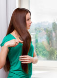 Womanl at the window. Woman at the window with brush Royalty Free Stock Photo