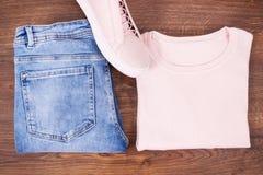 Womanly кожаные ботинки, брюки джинсов и свитер на деревенских досках стоковое изображение