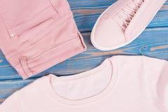 Womanly кожаные ботинки, свитер и брюки на старых голубых досках стоковые фотографии rf