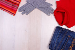 Womanly clothes on wooden background, copy space for text, clothing for autumn or winter. Womanly clothes on wooden board, gloves, turtleneck sweater, shawl or Stock Photography