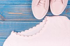 Womanly clothing and accessories on old boards, leather shoes and sweater. Womanly clothing and accessories on old boards, pink leather shoes and sweater Royalty Free Stock Photos